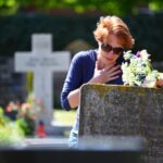 mourning/ woman mourning a deceased loved one on a graveyard